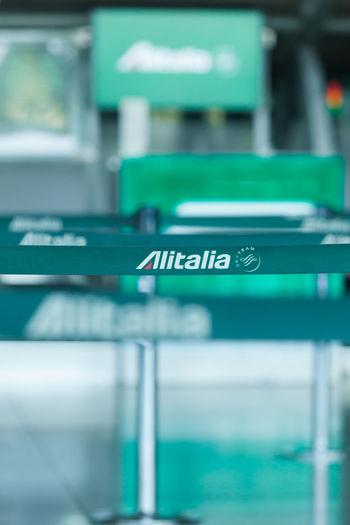 Business Company Logo Queuing Shallow Depth Of Field Air Carrier Airport Alitalia Close-up Flight Focus On Foreground Green Color Guidance No People Selective Focus Sign Text