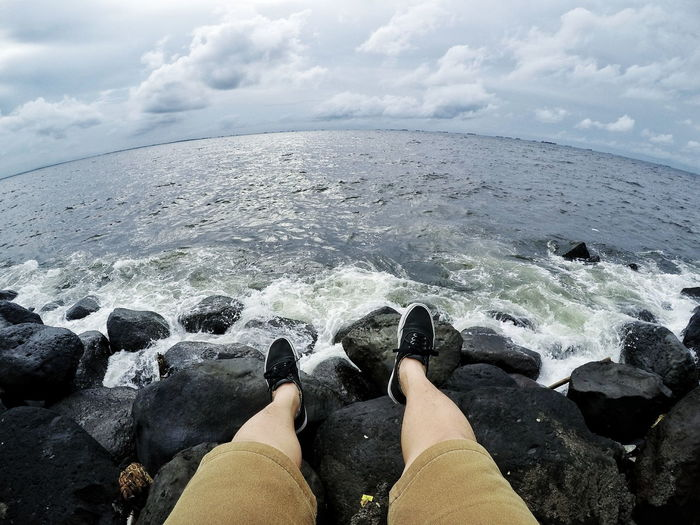 Fish eye view of person on rock by sea against cloudy sky