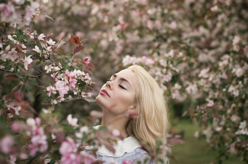 Young woman smelling flowers outdoors