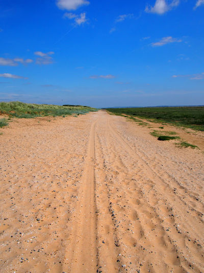 a straight long dry sand road with tire tracks and footprints extending to Country Road Dunes Grass Road Arid Climate Cloud - Sky Coast Direction Dirt Road Environment Horizon Landscape Nature Outdoors Road Sand Scenics - Nature Semi-arid Sky The Way Forward Tire Track Tracks Tyre Tracks vanishing point