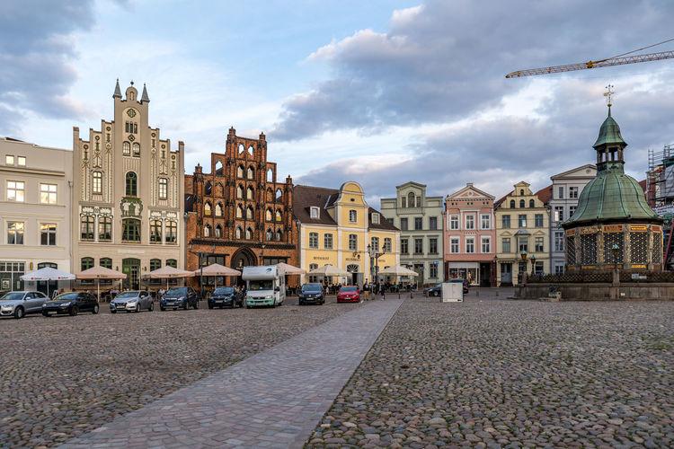 Buildings by road against sky in city