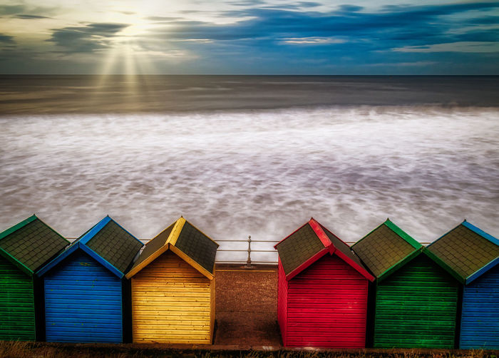 Beach Huts On Shore Against Sky During Sunset