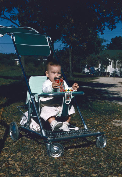 Baby holding Budweiser Budweiser Boys Casual Clothing Child Childhood Day Front View Full Length Innocence Leisure Activity Lifestyles Males  Men Music Nature One Person Outdoors Plant Pre-adolescent Child Real People Sitting Stroller