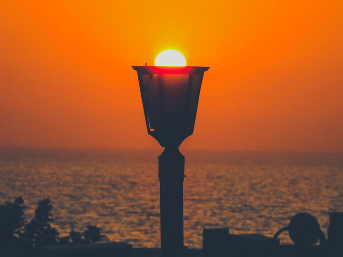 Illuminated lamp by sea against orange sky