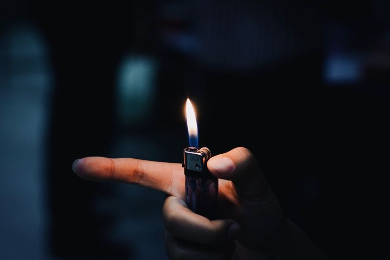 Close-up of hand holding burning cigarette lighter at night