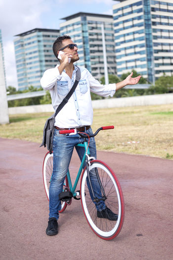 Mid adult man with bicycle talking on mobile phone while standing against buildings