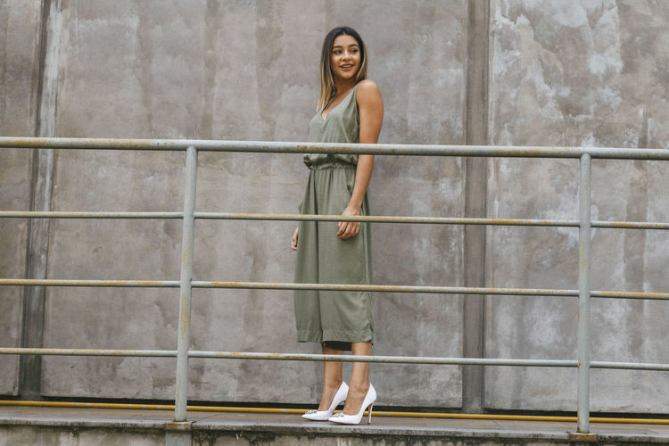 Full Length Of Fashionable Young Woman Standing By Railing Against Concrete Wall