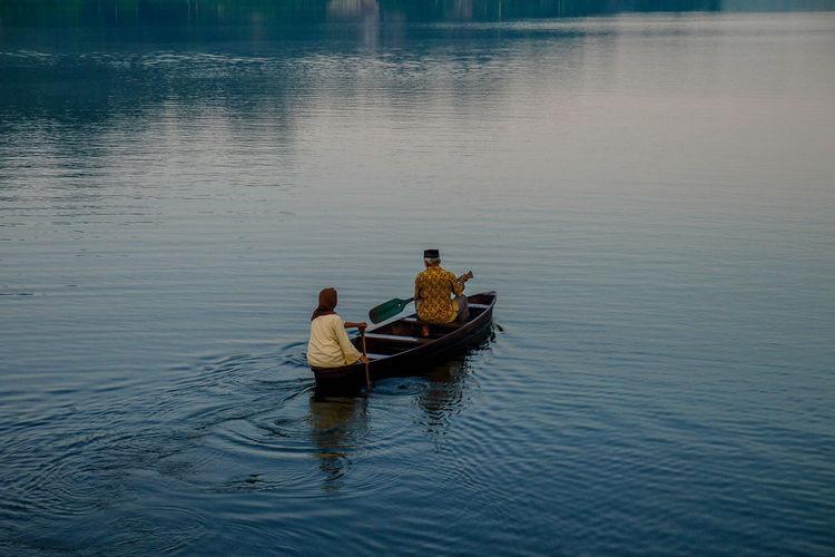 Rear view of men sitting on boat in lake