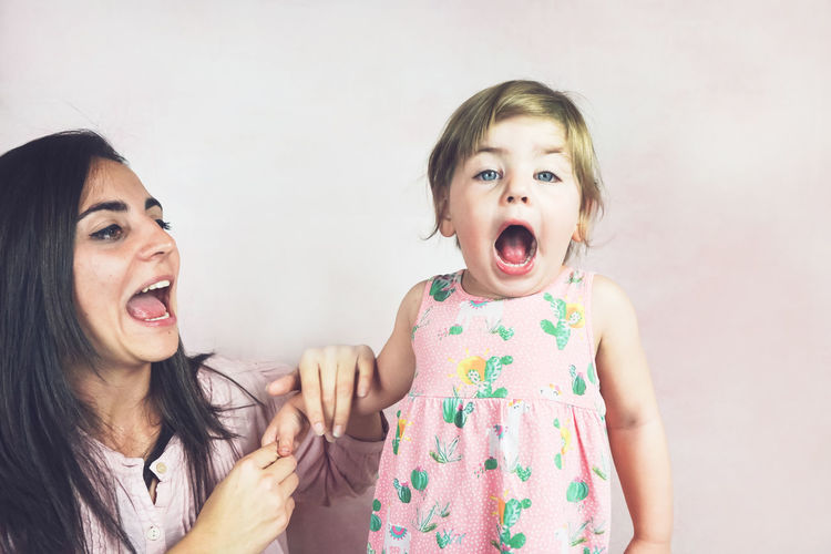 Two People Mouth Open Mouth Emotion Togetherness Childhood Portrait Women Child Indoors  Females Headshot Bonding Front View Family Girls Casual Clothing Real People Positive Emotion Innocence Sister Hairstyle Scream Screaming Moth