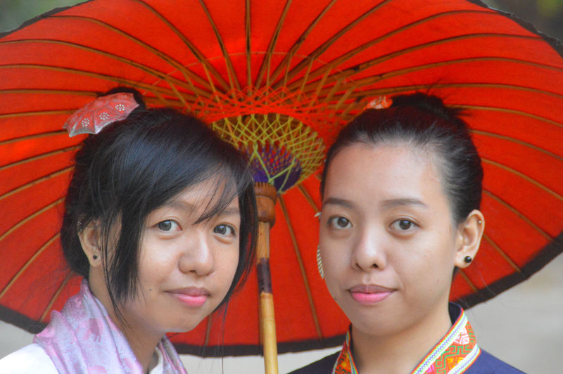 Close-up portrait of smiling women under umbrella