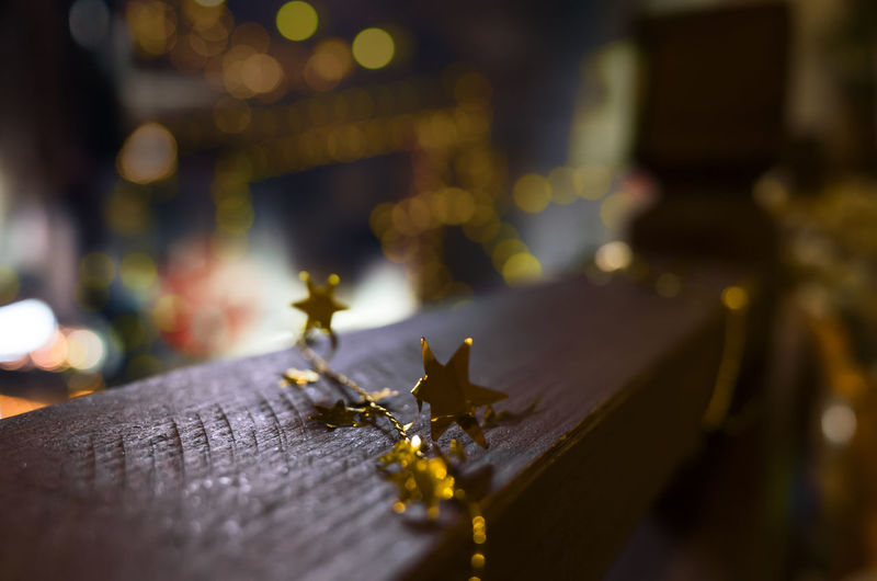 Close-Up Of Gold Star Shape Decorations On Railing During Christmas