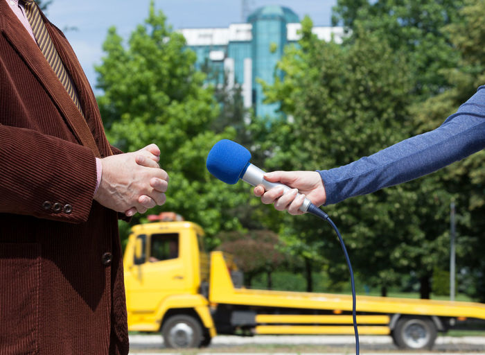 Cropped hand holding microphone by businessman during interview
