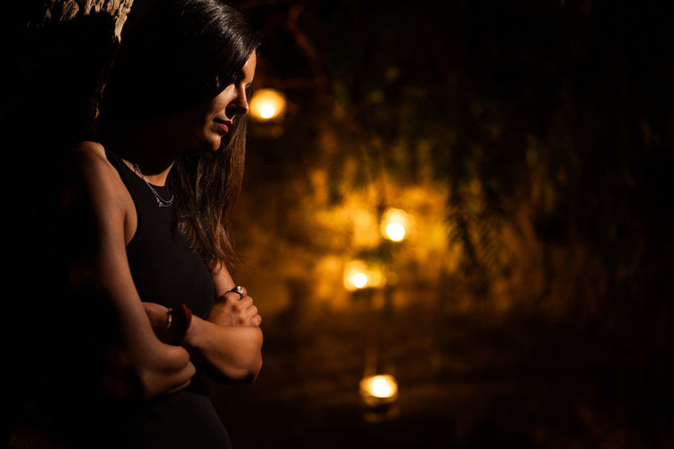 Portrait of young woman looking at illuminated camera at night