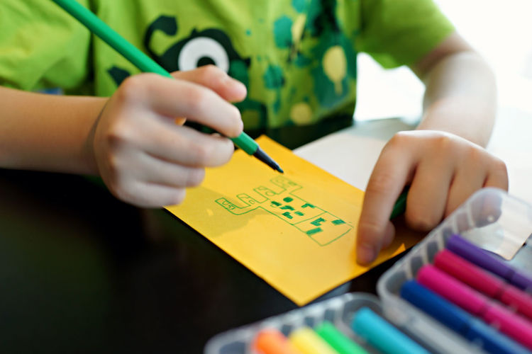 Close-up of child hands drawing on color paper Children Colors Doodle Having Fun Kids Practice Artclass Childhood Doodling Draw Drawing Education Hand Holding Mammal One Person Paper Table