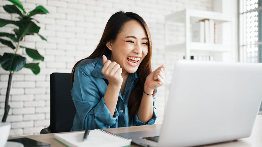 Happy young woman using phone while sitting on table