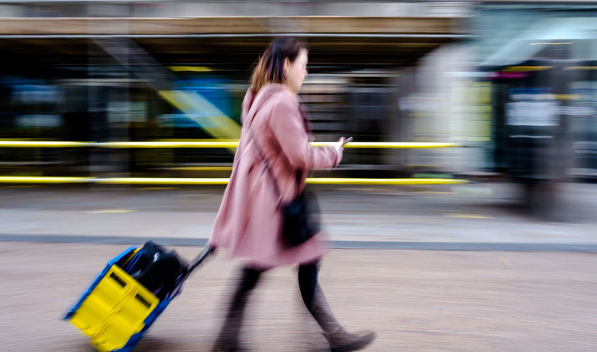 Blurred Motion Of Woman With Luggage Walking On Road In City