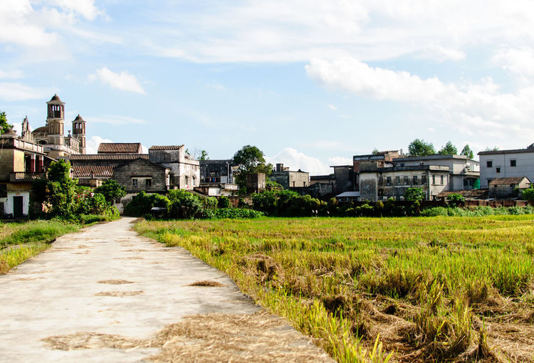 Narrow pathway leading towards houses against sky