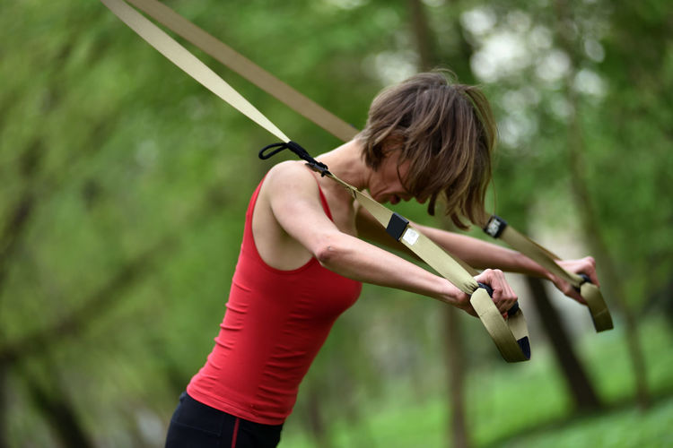 Mid adult woman exercising at public park