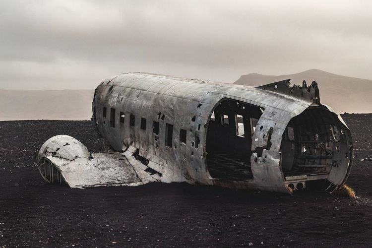 Abandoned Airplane On Ground Against Sky