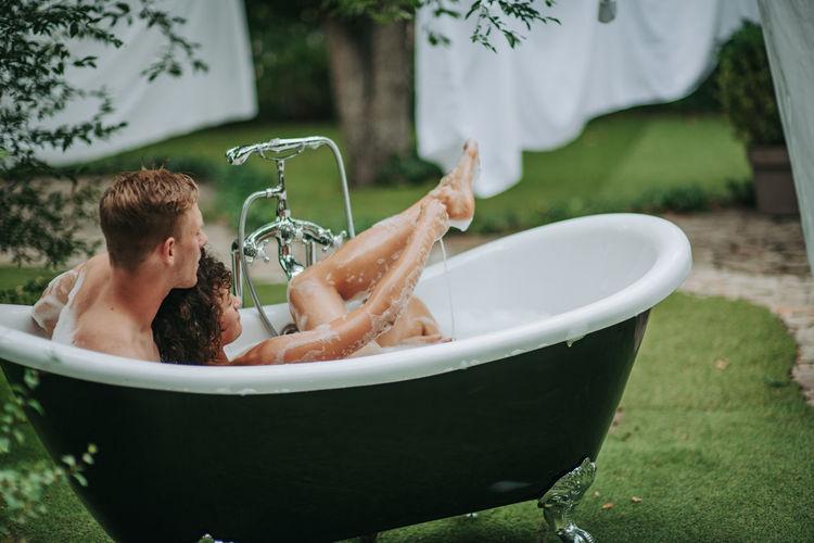 Full length of shirtless man in bathtub