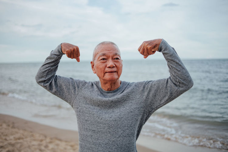 60 70 Chinese Yoga Active Adult ASIA Asian  Athletic Beach Exercise Exercising Father Fit Grandfather Gray Grey Hair Happiness Healthy Holiday Japanese  Lifestyle Male Man Nature Ocean Old Outdoor Outdoors People person Portrait Positive Retirement Sand Sea Seaside Senior Sixties Slim Sport Stretch Stretching Summer Tai Chi Training Water Workout