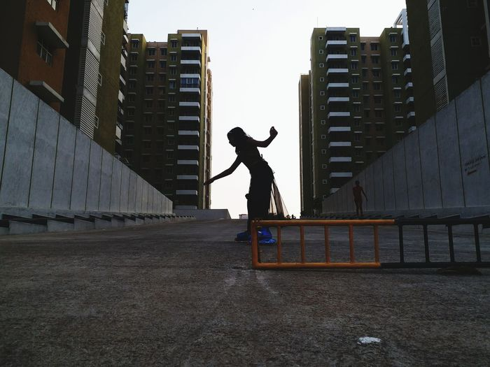 Full Length Side View Of Girl Skating On Concrete Amidst Buildings In City