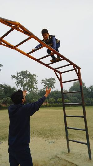 Father and son playing with outdoor play equipment at playground