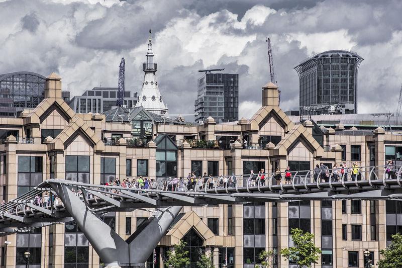 People On London Millennium Footbridge Against Buildings In City