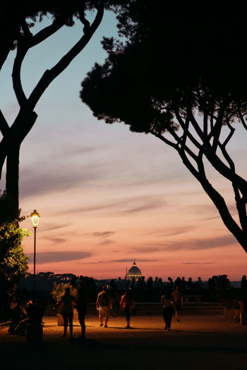 Silhouette people by tree against sky during sunset
