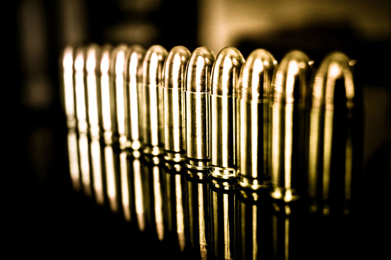All lined up and ready to go Perspective Reflection Straight Bullet Close-up Day Depth Of Field Full Metal Jacket Gold Colored High Definition Indoors  Lines And Shapes Metal No People Pistol Selective Focus 45 Reflections Piano Contrast Light And Shadow Smooth Texture See The Light