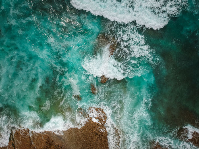 Aerial view of ocean waves and brown rocks in the coastline Aquatic Sport Beach Beauty In Nature Breaking Bwach Day Dronephotography High Angle View Motion Nature No People Outdoors Power Power In Nature Rock Rock - Object Sea Seascape Solid Sport Turquoise Colored Water Wave Waves Waves, Ocean, Nature