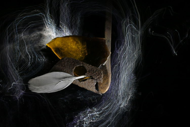 Close-up of rusty metal with feather over light painting against black background