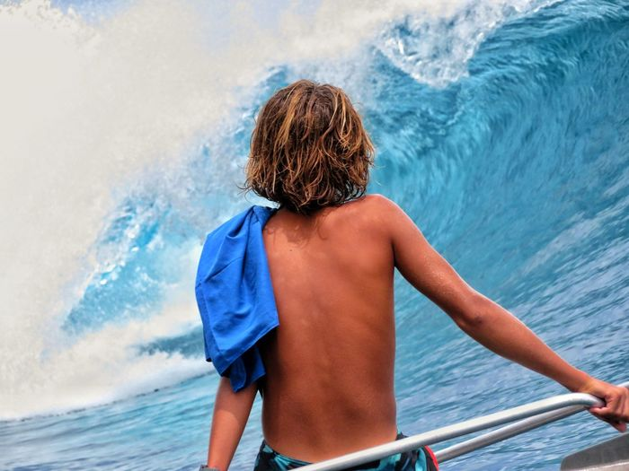 Rear view of shirtless boy in sea against sky