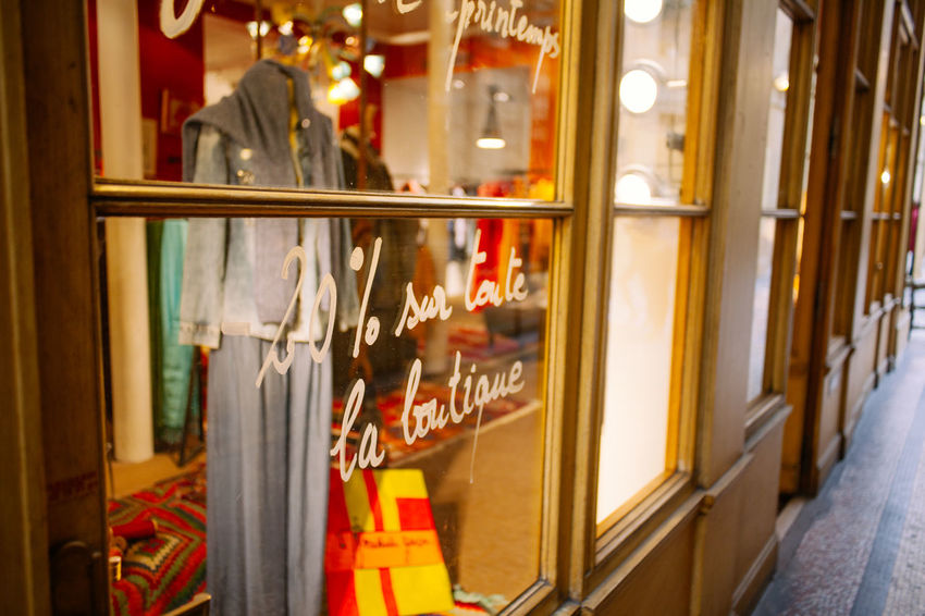 A discount announcement stick on glass window of Paris Architecture Capital Cities  City City Life Cosy Discount Dress Fashion France French Galerie Vivienne Paris Shopping Store Trend Warm Window Wooden