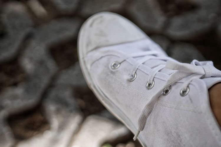Low section of person wearing white shoes