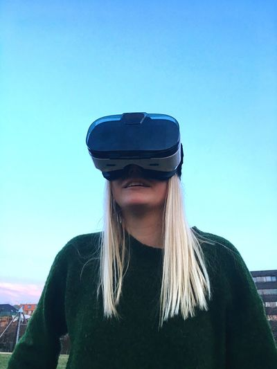 Low angle view of woman using virtual reality simulator against clear blue sky