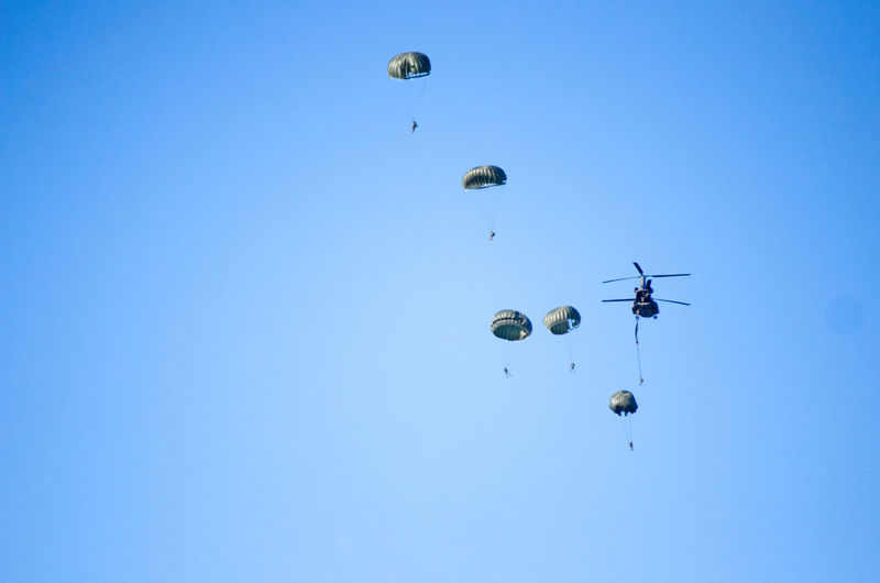 Low angle view of helicopter with parachutes in clear blue sky