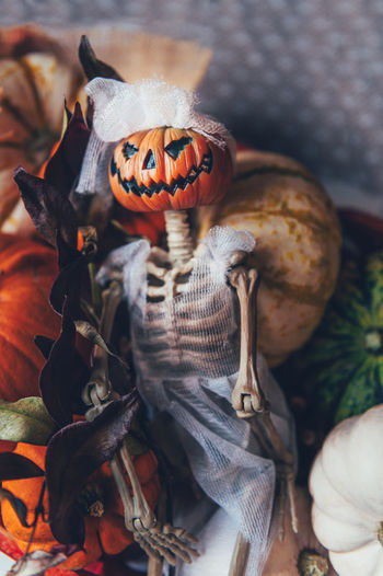 Different types of pumpkins and decorations in the box. skeleton with pumpkin head in bridal oufit