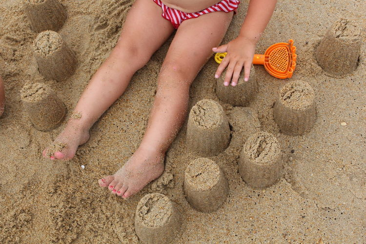 Low section of girl playing on beach