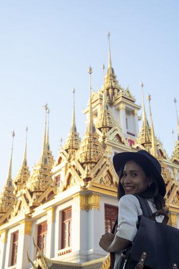 Portrait of a smiling temple against building