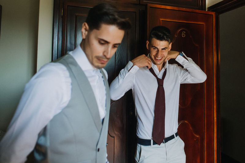 Groom and friend getting dressed at home