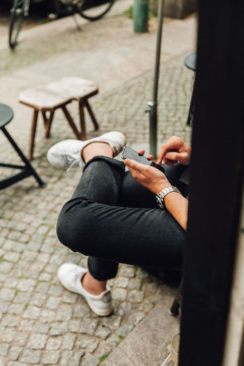 Midsection of man using mobile phone while sitting on seat