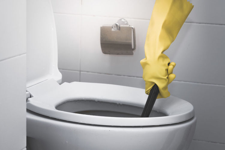 Cropped hand of person wearing yellow protective glove while washing toilet bowl