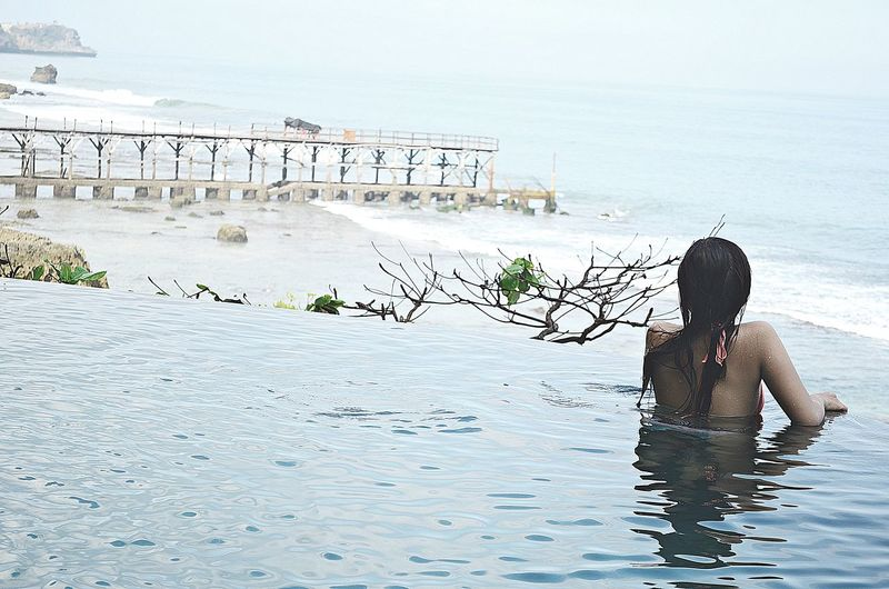 Rear view of woman in infinity pool at beach