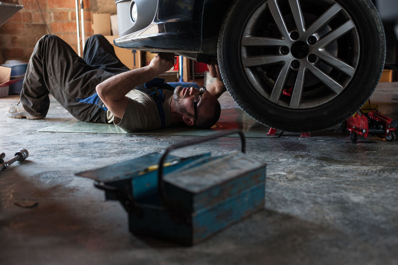 Man fixing a car at home Auto Repair Shop Car Day Full Length Garage Indoors  Lying Down Mechanic Men Mode Of Transportation Occupation One Person Real People Repairing Selective Focus Shopping Tire Transportation Wheel Working Workshop