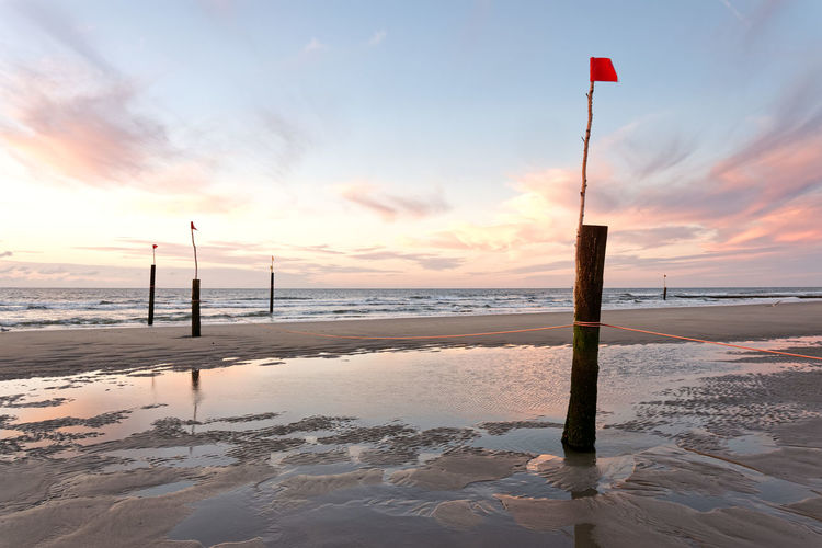 Sunset on a beach with reflections in the ocean Reflection Ocean Fine Art Coast Coastline Shore Photography Island Fine Art Photography Fineart Print Poster Nordsee Northsea Germany Sunset Water Sea Beach Sunset Wooden Post Sand Lighthouse Sky Horizon Over Water Cloud - Sky Low Tide Pole Flag Calm