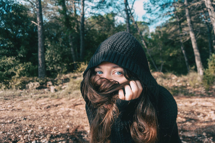 Portrait Of Young Woman Covering Face With Hair In Forest