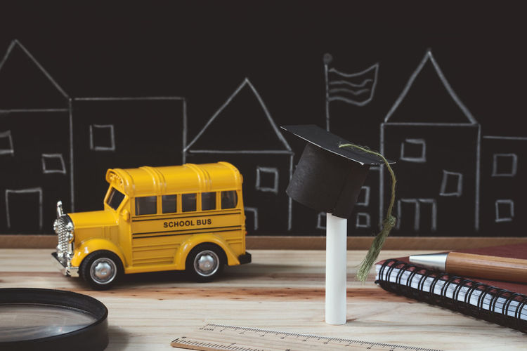 Education concept. Desk Graduating Graduation Student Wood Blackboard  Book Business Car Chalk Chalkboard City Creativity Education Educational Land Vehicle Magnifying Glass Mortar Board Pen School School Bus Success Table Toy Wooden