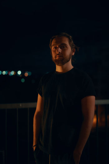 Portrait of young man standing at night