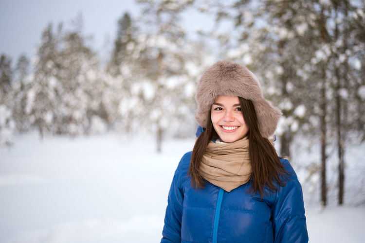 Beautiful European girl walking on skis in the woods on a snowy winter day Winter Cold Temperature Snow One Person Warm Clothing Woman Activity Outdoors Ski Smile Sport Park Forest Caucasian Blue Hat Earflaps Healthy Lifestyle Lifestyle Tree Beautiful Skiing Adventure White Happiness Weekend